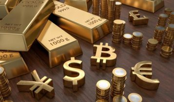 Gold bars and coins with gold currency symbols