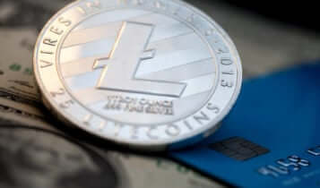 litecoin coin with a card and a dollar bill on the background