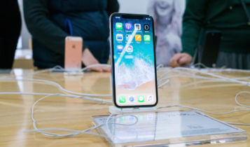 iphone x displayed on a clear stand on a table and two people in the background