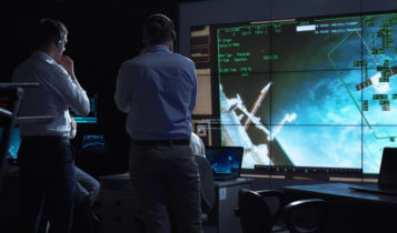 people analyzing with their computers and a screen that shows a spacecraft with numbers