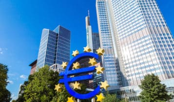 the euro logo and the european central bank headquarters behind it