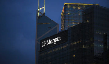 JPMorgan logo on a bulding with 2 other buildings on the background and a dark sky
