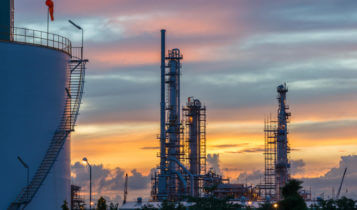 An oil refinary with blue and orange sky as a background