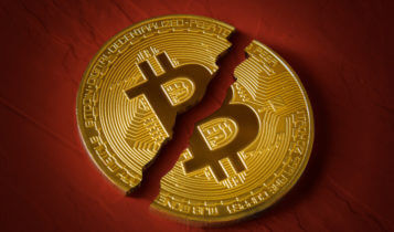 a bitcoin broken in half with a maroon background