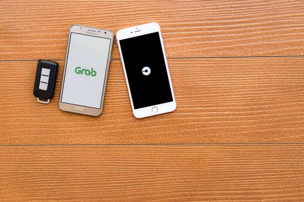2 smartphones side by side, as the 1st phone has Grab on its screen, while the other is Uber