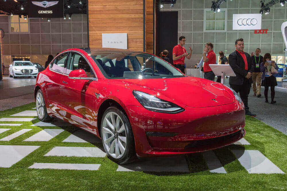 A Tesla Model 3 is being displayed in a showroom