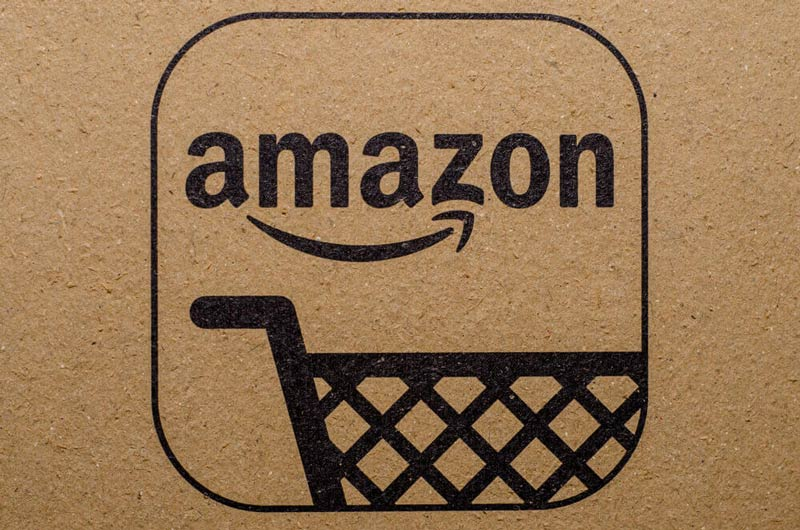 amazon logo inside of a square as the background is a texture of a cardboard