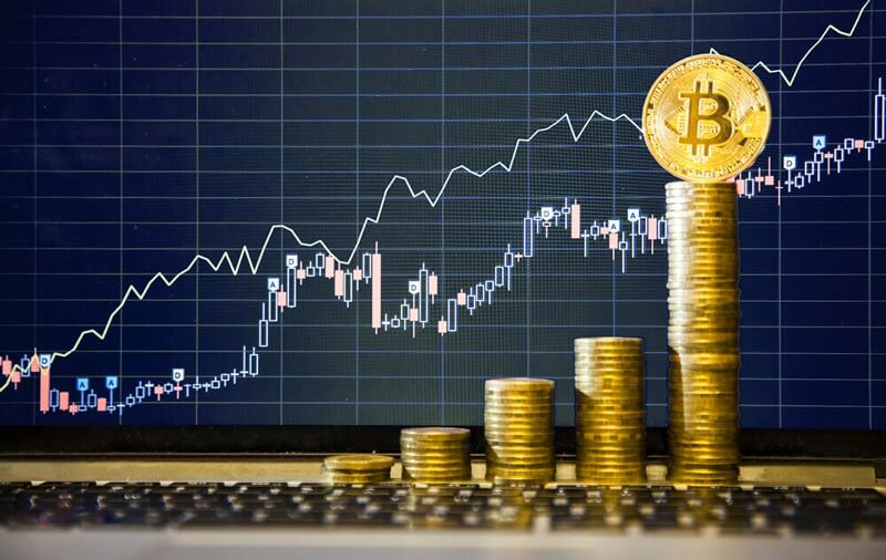 coins stacked in an ascending manner, and a bitcoin stands on the tallest column.