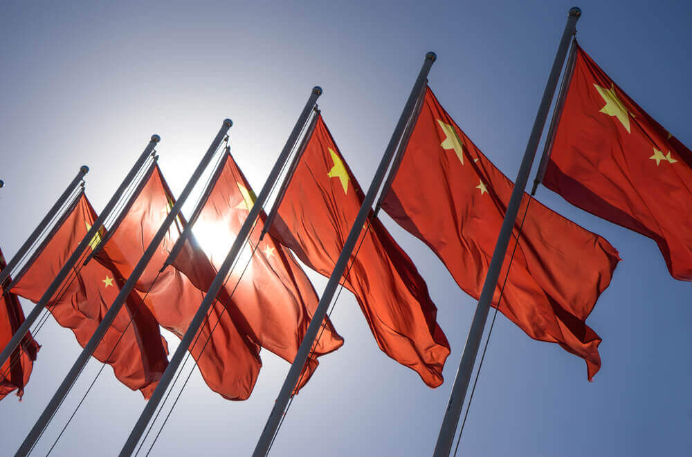 Row of flags of china with the sky as a background