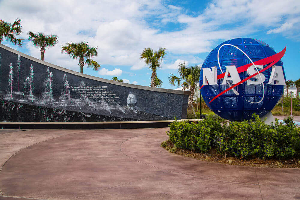 a facility of NASA with its logo showing and shrubs below it