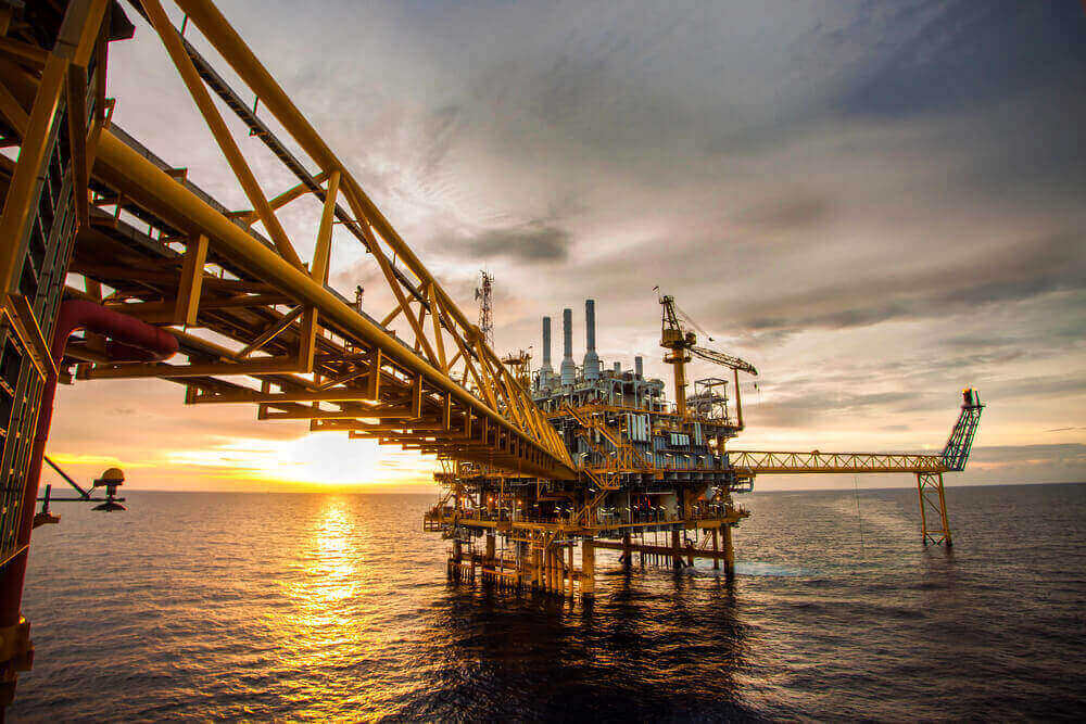 An oil refinary on a sea with a sunset background