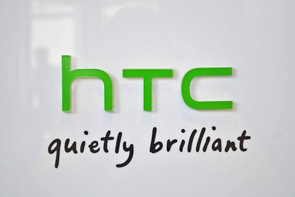 logo of HTC with its slogan quitely brilliant below it and white glass background