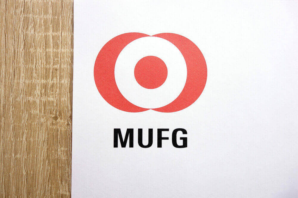 MUFG logo drawn on a white background with a wooden texture left side