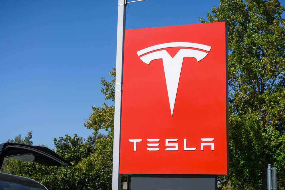 a red sign with the tesla logo on it
