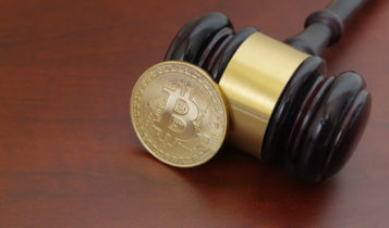 bitcoin in a form of coin leaning on a wooden gaven on wooden surface