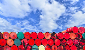 oil barrels stacked on top of each other with a blue sky as a background