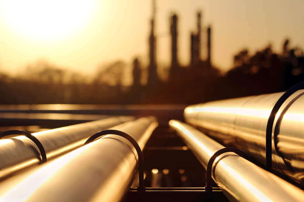 oil pipes with a silhouette view of a refinery
