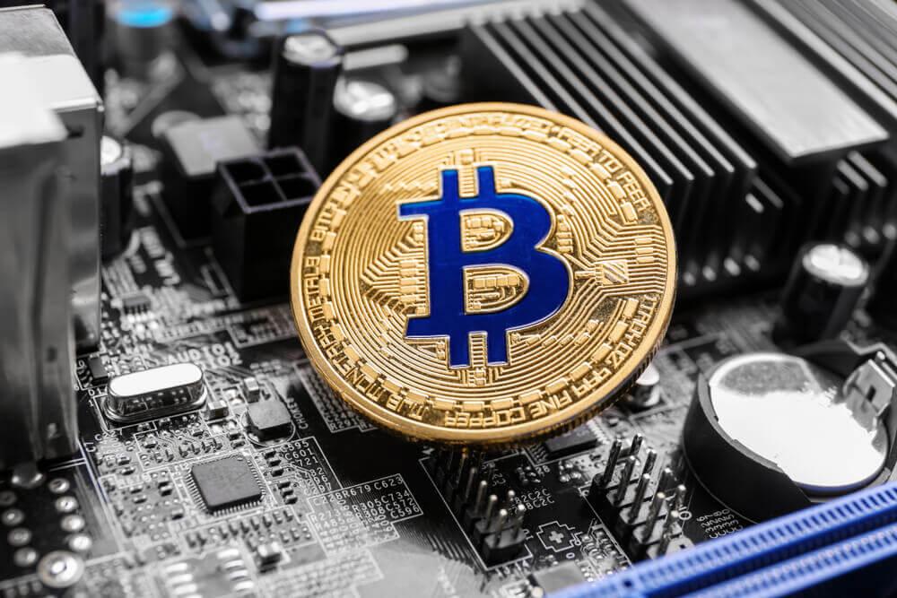 moeda de bitcoin com placa mãe ao fundo