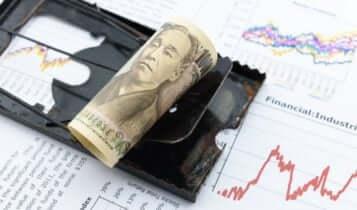 Finance Brokerage – Abenomics: Rolled-up Japanese yen banknote on financial data.