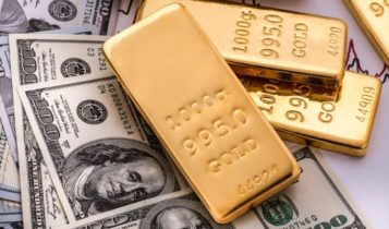 Finance brokerage-Oil Inventory Reports: Gold bars on top of a pile of dollar bills.