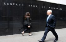 Finance Brokerage - foreign exchange trading: Man and woman in suit walking in front of the Reserve Bank of Australia