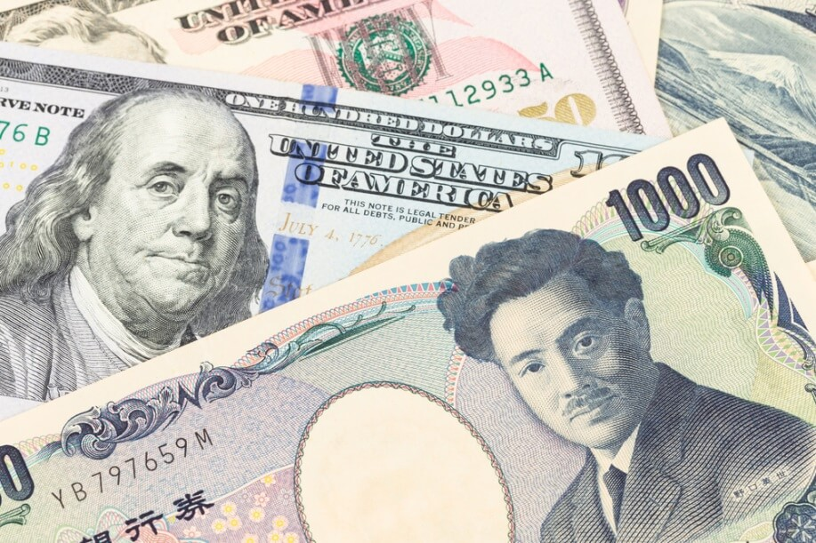 Finance Brokerage – Foreign exchanges trading: Dollar and yen banknotes stacked on top of each other.