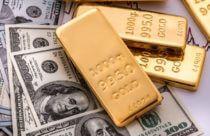 Finance Brokerage – gold spot price: overhead shot of gold bars on top of dollar bills.