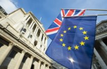 Finance Brokerage – Britain: an undershot view of the Bank of England with the British and European flags on the foreground.