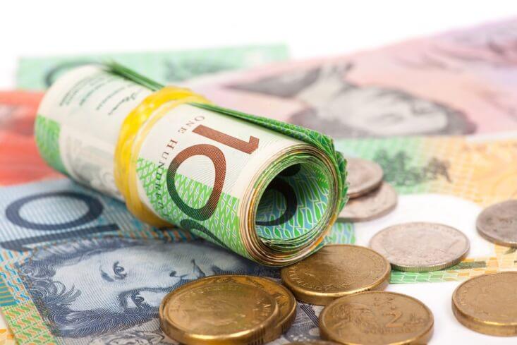 Rolled up Aussie dollar bills with coins