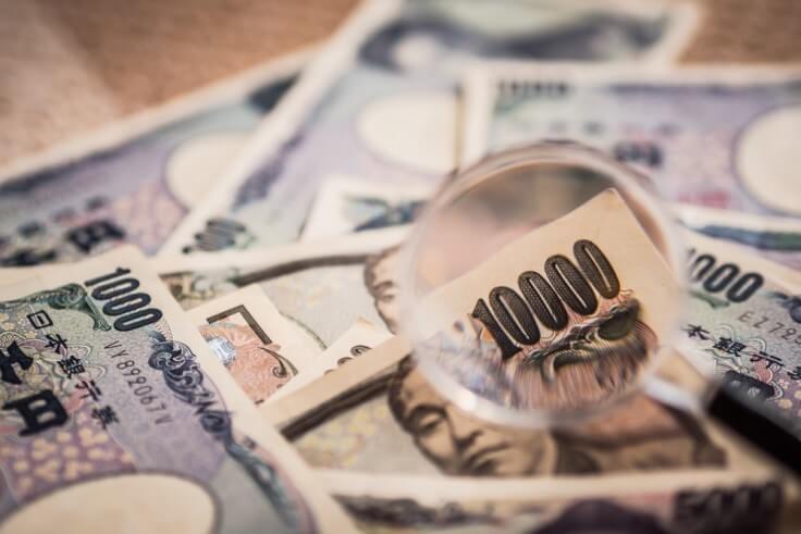 Finance Brokerage-Market Sentiment: yen banknote under a magnifying glass