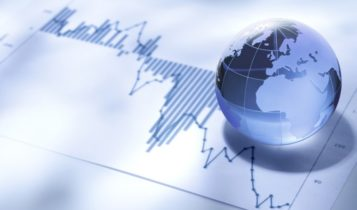 Finance Brokerage-Market Sentiment: small glass globe on top of paper with graphs and charts