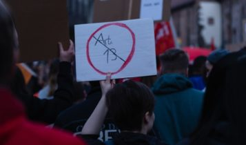 """Finance Brokerage-Copyrights: protester holding placard with """"Art. 13"""" written and crossed out"""