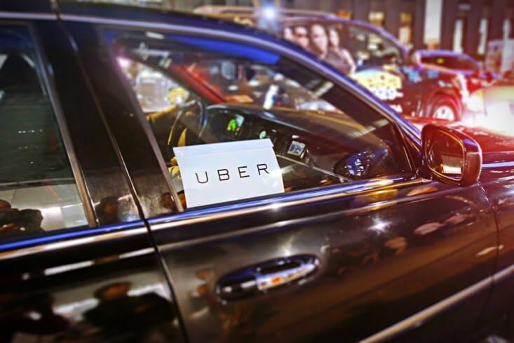 A photograph of the Uber logo with black car.