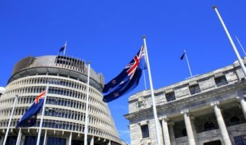 Finance Brokerage-New Zealand Government: Outside shot of the New Zealand parliament with the country's flag in the foreground