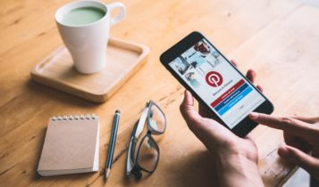 Finance Brokerage-Pinterest: a hand using mobile phone for accessing Pinterest