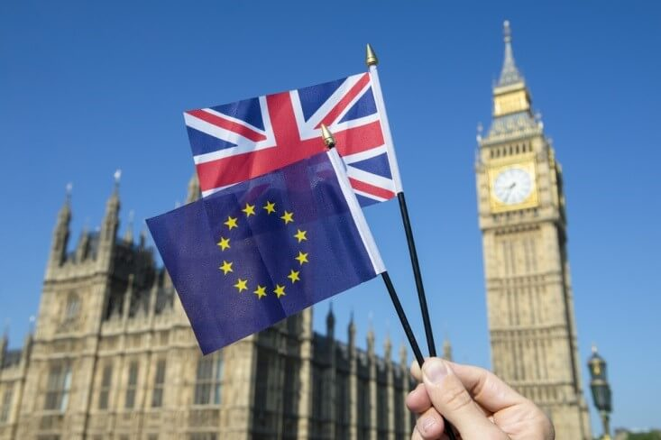 Finance Brokerage-Trade Agreement: hand waving mini flags of the UK and EU with the British Parliament and Big Ben on the background