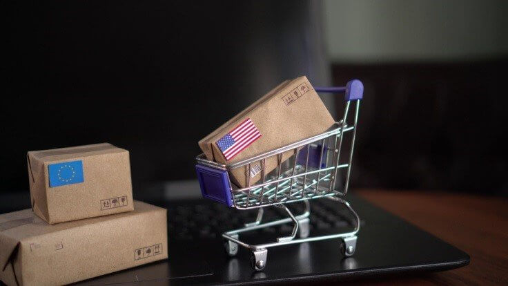 Finance Brokerage-Trade Agreement: Miniature boxes with US and EU flags pasted. US box on a miniature shopping cart.