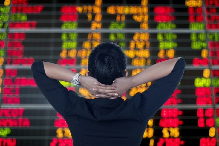 Stock Exchanges – a woman touching the back of her head with two hands as she stares on stock tickers – Finance Brokerage
