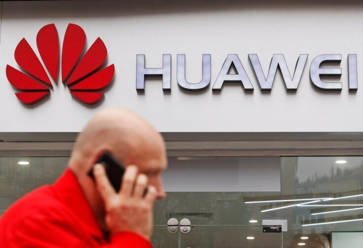 Huawei – a shot of a person using his phone with Huawei store behind on the background – Finance Brokerage