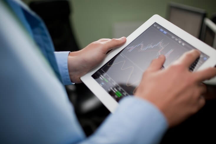 Share Market – a man holding a tablet and checking out graphs and charts from stock market - Finance Brokerage