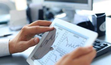 Фондовые рынки – фото мужчины, держащего в руках планшет, на экране которого показаны биржевые графики – Finance Brokerage