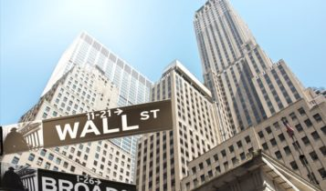 US Federal Reserve – Wall Street street sign with buildings on the background – Finance Brokerage
