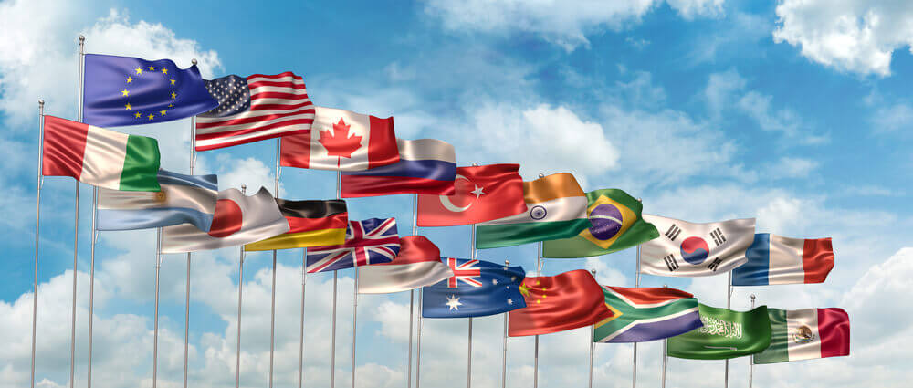 Flags of countries members of G20 waving against blue sky