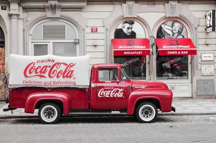 Finance Brokerage –: A Coca Cola truck parked outside a storefront.