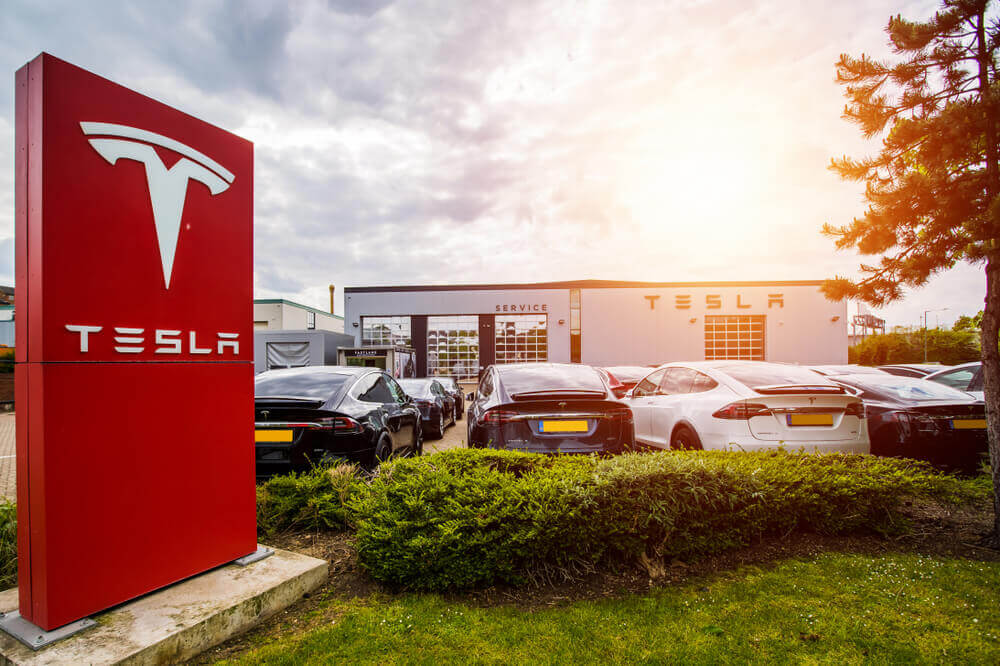 Finance Brokerage – Tesla shares: Tesla building with logo and cars.