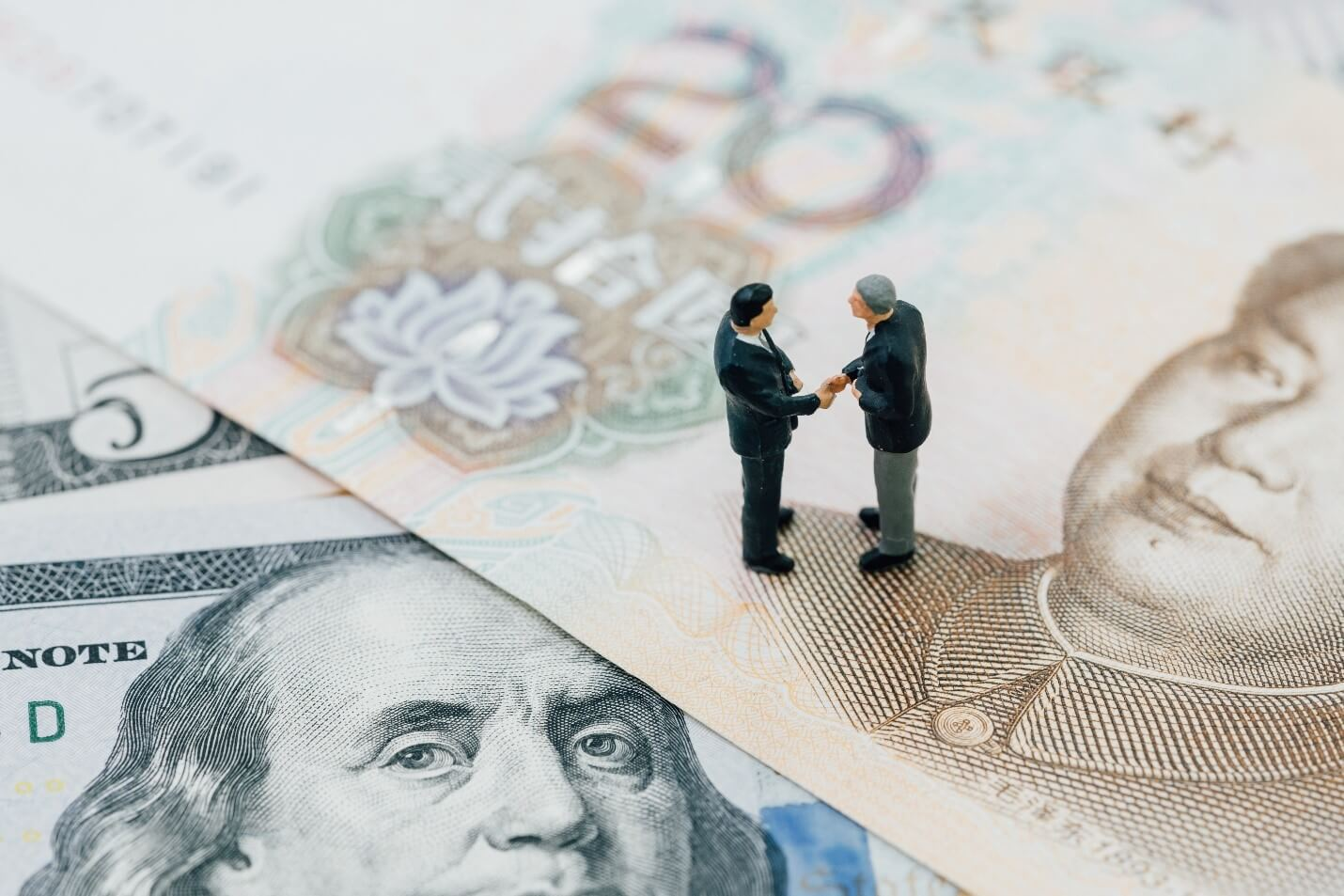 Two small figurines shaking hands over a yuan and dollar bill