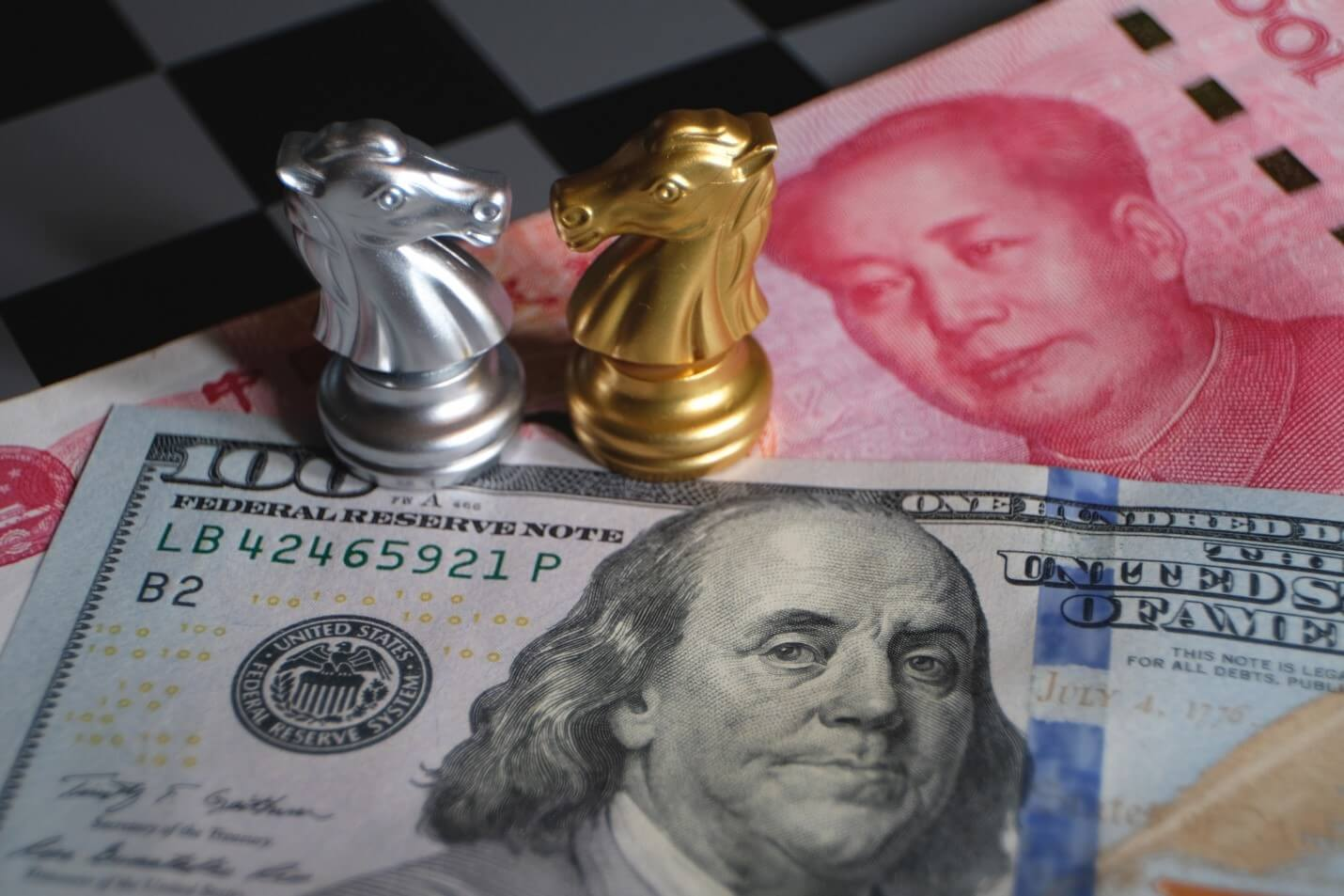 Two chess pieces over a dollar and yuan bill