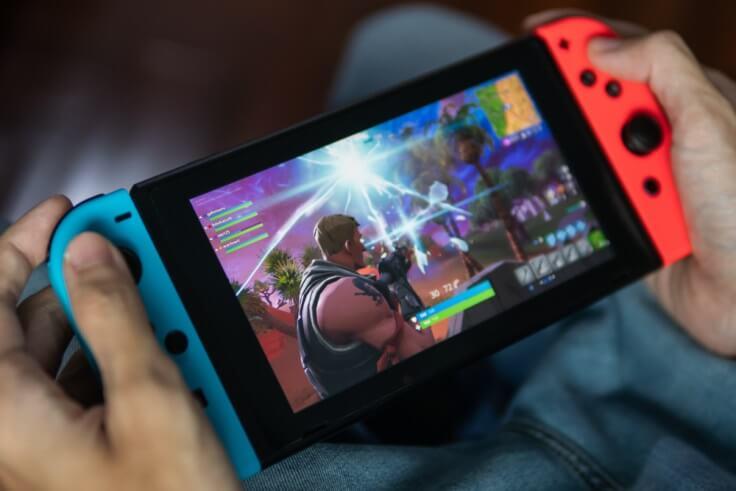 Nintendo Switch between two hands – Finance Brokerage