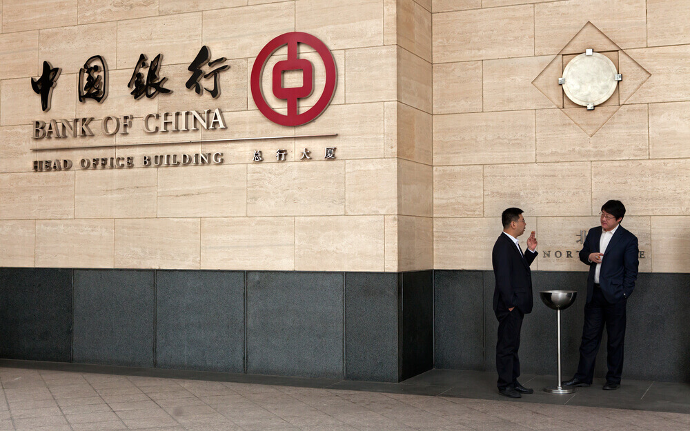 Finance Brokerage – SZSE: Bank of China headquarters with two men in side.