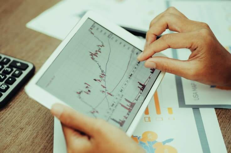 charts on tablet with hand – Finance Brokerage